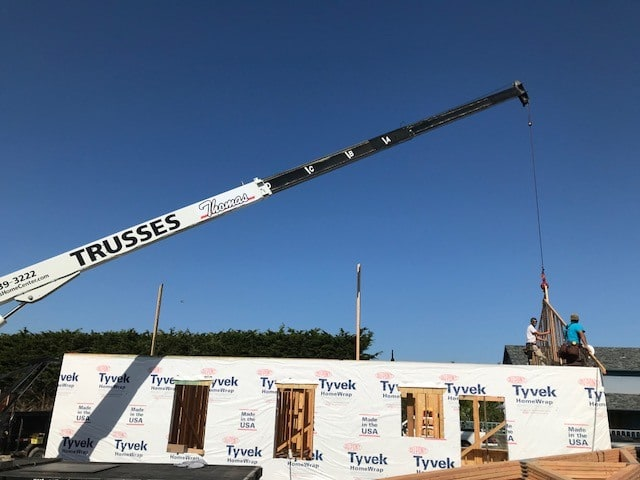 crane lower roof trusses onto new home