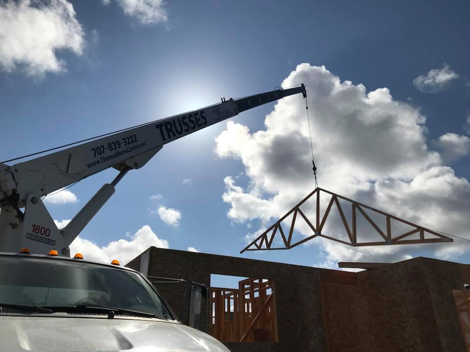 new home construction with crane lowering roofing truss